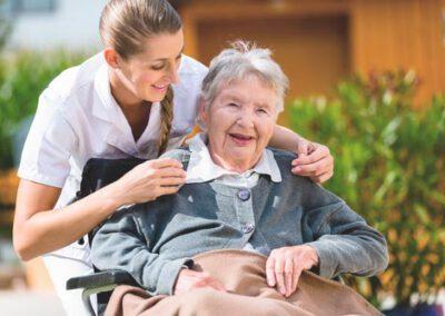 Pflegerin macht Spaziergang mit Seniorin im Rollstuhl